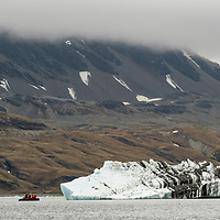 An inflatable boat is dwarfed by a glacial iceberg from the Nordenskjold Glacier in Cumberland East Bay on the north coast of South Georgia Island.