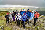 Our group stands on Kidsty Pike (780 m or 2560 ft), the highest point on the England Coast to Coast hike. Below, see Haweswater Reservoir, in Lake District National Park, Cumbria county, England, United Kingdom, Europe. Today, day 6 of 14 trekking Coast to Coast, we went from Ullswater to Kirkby Stephen. Hiking 10 miles with 2600 feet cumulative gain in the fells of Lakeland brought us over the highest Roman road in England, then down to the lakeshore of Haweswater. Overnight in Brownber Hall Country House near Kirkby Stephen. [This image, commissioned by Wilderness Travel, is not available to any other agency providing group travel in the UK, but may otherwise be licensable from Tom Dempsey – please inquire at PhotoSeek.com.]