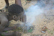 Africa, Tanzania, Lake Eyasi, young male Hadza child lights a fire. Hadza, or Hadzabe, are an indigenous ethnic group in north-central Tanzania, living around Lake Eyasi in the central Rift Valley and in the neighboring Serengeti Plateau