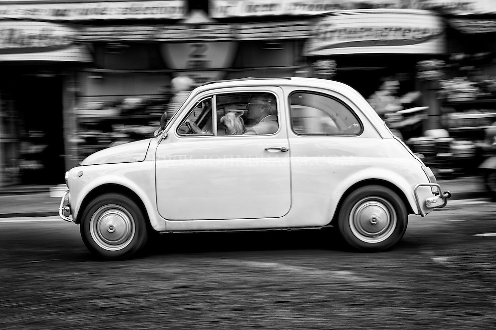 Black and white photo of a man driving a Fiat 500 in Sorrento, Italy with a dog sitting in his lap.