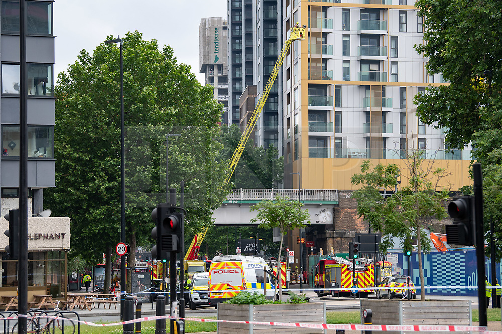 """© Licensed to London News Pictures. 28/06/2021. London, UK. Emergency services including an aerial ladder from London Fire Brigade at the scene. One hundred firefighters tackled a fire near Elephant and Castle railway station in southeast London. London Fire Brigade (LFB) said three commercial units in railway arches were """"completely alight"""", in addition to six cars and a telephone box. Photo credit: Peter Manning/LNP"""