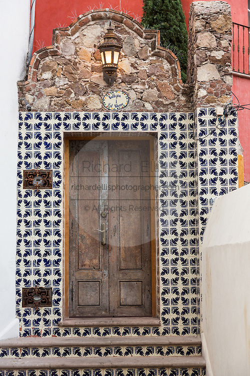 A traditional hacienda style wooden door and Spanish colonial tile on a historic home in San Miguel de Allende, Mexico.