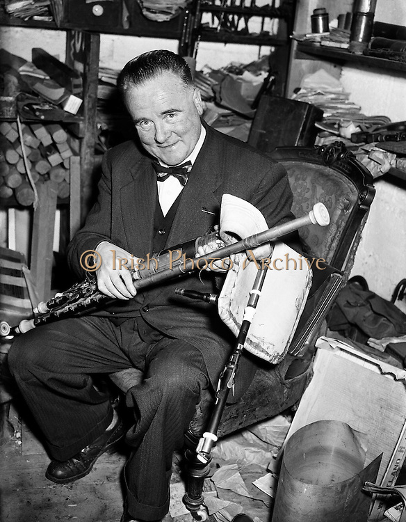 """Leo Rowsome making pipes at 9 Belton Park Road.16/06/56..Leo Rowsome (05/04/1903 - 20/09/1970) was the third generation of an unbroken line of uilleann pipers. He was performer, manufacturer and teacher of the uilleann pipes - the complete master of his instrument. He devoted his entire life to the uilleann pipes..Samuel Rowsome, Leo's grandfather sent his sons, John, Thomas and William to a German teacher of music who resided in Ferns, near their home in Co. Wexford to learn the theory of music and how to play various instruments. This knowledge was passed on through William to his son, Leo who made good use of it in his teaching, writing music for his many pupils..Leo was born in Harold's Cross, Dublin in 1903. His father, William realised that his son had the ability to become a talented musician and craftsman. Constantly watching his father making and repairing instruments, Leo learned the art of pipe making and instrument repair. So rapid was his progress at piping that in 1919 at the age of sixteen he was appointed teacher of the uilleann pipes at Dublin's Municipal School of Music (now D.I.T. Conservatory of Music & Drama) for 50 years. He also taught at Dublin's Pipers Club of which he was President..In 1925, Leo's father died at the age of fifty-five. Leo successfully carried on the family business, after completing his own set of pipes in 1926. The instrument remained an object of fascination and veneration for countless audiences at home and abroad..Leo was the first uilleann piper to perform on Irish National Radio in the early 1920s when he played solo and later in duets with Frank O'Higgins (fiddle), Micheal O Duinn (fiddle) and Leo's brother John (fiddle). Leo's """"All Ireland Trio"""" comprised Neilus Cronin, flute, Seamus O'Mahony, fiddle and Leo pipes. He formed his Pipes Quartet in the mid 1930s and broadcast regularly throughout the 1940s/50s. Leo was the first Irish artist to perform on BBC T.V. (1933). He made many recordings for Dec"""