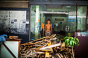 """12 DECEMBER 2012 - BANGKOK, THAILAND: A worker stands in the doorway of the former brothel he lives in at """"Washington Square"""" a notorious entertainment district off Sukhumvit Soi 22 in Bangkok. Demolition workers on many projects in Thailand live on their job site tearing down the building and recycling what can recycled as they do so until the site is no longer inhabitable. They sleep on the floors in the buildings or sometimes in tents, cooking on gas or charcoal stoves working from morning till dark. Sometimes families live and work together, other times just men. Washington Square was one of Bangkok's oldest red light districts. It was closed early 2012 and is being torn down to make way for redevelopment.    PHOTO BY JACK KURTZ"""