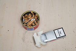 Makeshift ashtray full of cigarette butts next to an empty packet of cigarettes showing the message smoking kills,