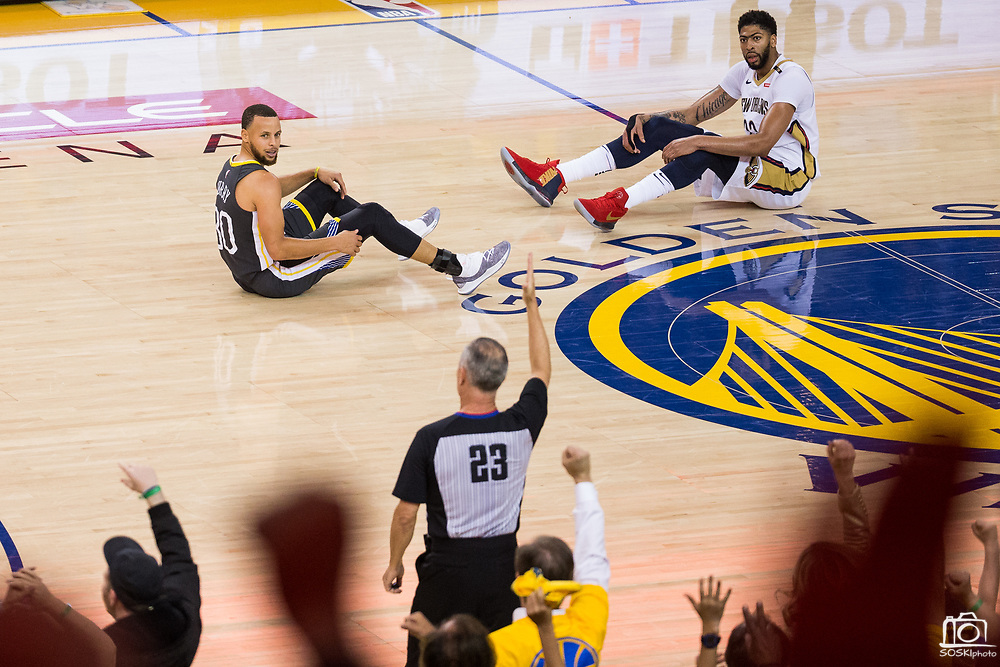 Golden State Warriors guard Stephen Curry (30) sits on the court after colliding with New Orleans Pelicans forward Anthony Davis (23) at the end of the second quarter at Oracle Arena during Game 2 of the Western Semifinals in Oakland, California, on May 1, 2018. (Stan Olszewski/Special to S.F. Examiner)