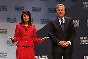 Republican presidential candidate Gov. Jeb Bush smiles as South Carolina Gov. Nikki Haley asks him a question at the Heritage Foundation Take Back America candidate forum September 18, 2015 in Greenville, South Carolina. The event features 11 presidential candidates but Trump unexpectedly cancelled at the last minute.