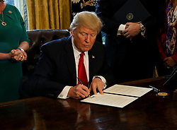 Washington, DC - February 3, 2017; U.S. President Donald Trump signs an Executive Order in the Oval Office of the White House, to review the Dodd-Frank Wall Street to roll back financial regulations of the Obama era.