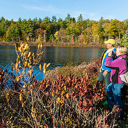 A couple watches for birds at Round Pond in Barrington, New Hampshire.