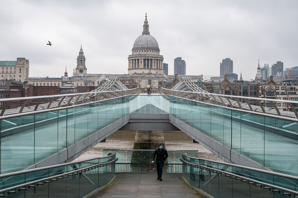 © Licensed to London News Pictures. 01/02/2021. London, UK. A man wearing a face mask walks across the Millennium Bridge on the River Thames. London is currently in Tier-4 advising people to stay at home. Today marked the 1st anniversary of first UK Covid-19 person. Since then, over, 100,000 people have died in the UK with the Covid-19 disease. Photo credit: Ray Tang/LNP