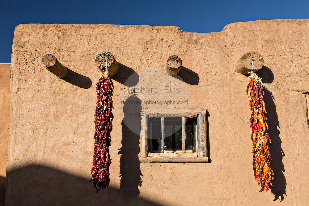 Dried chile pepper ristras hang on an adobe wall at the ancient Native American Taos Pueblo outside Taos, New Mexico. The pueblos are considered to be one of the oldest continuously inhabited communities in the United States and is designated a UNESCO World Heritage Site.