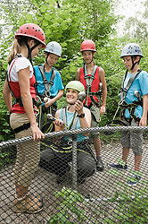 Young woman giving instruction to childrens for climbing crag