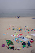 Abandoned possesions of rucksacks, shoes, buckets, spades and towels belonging to a group of young schoolchildren and their carers, as they go to paddle in the sea, on 18th July 2016, at Barra, near Aveira, Portugal.