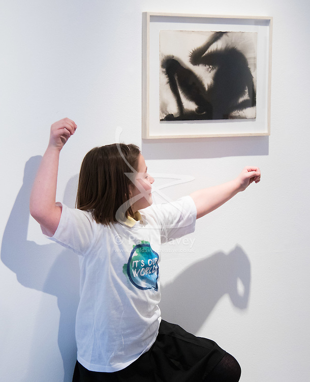 """Christies, St James, London, March 4th 2016. Nine year-old Ashley Hubbard from Charlton Manor Primary School mimics the shadowy shapes in  Sir Anthony Gormley's """"Wound"""" from 2014, at the preview for the It's Our World charity auction at Christie's. Over 40 leading artists including David Hockney, Sir Antony Gormley, David Nash, Sir Peter Blake, Yinka Shonibare, Sir Quentin Blake, Emily Young and Maggi Hambling have committed artworks to the It's Our World Auction in support of The Big Draw and Jupiter Artland Foundation, to be sold at Christie's London on 10 March 2016.<br />  ///FOR LICENCING CONTACT: paul@pauldaveycreative.co.uk TEL:+44 (0) 7966 016 296 or +44 (0) 20 8969 6875. ©2015 Paul R Davey. All rights reserved."""