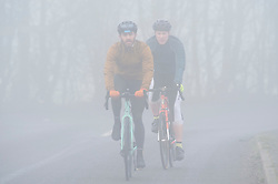© Licensed to London News Pictures. 22/02/2019. Swanley,Cyclists keeping fit in the fog on Crockenhill Lane,Kent. Heavy foggy weather this morning on the M25 at Swanley J3 in Kent.  Photo credit: Grant Falvey/LNP