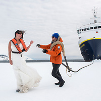 A newlywed couple on their Honeymoon pose on the fast ice by the National Geographic Explorer while in Crystal Sound, Antarctica.