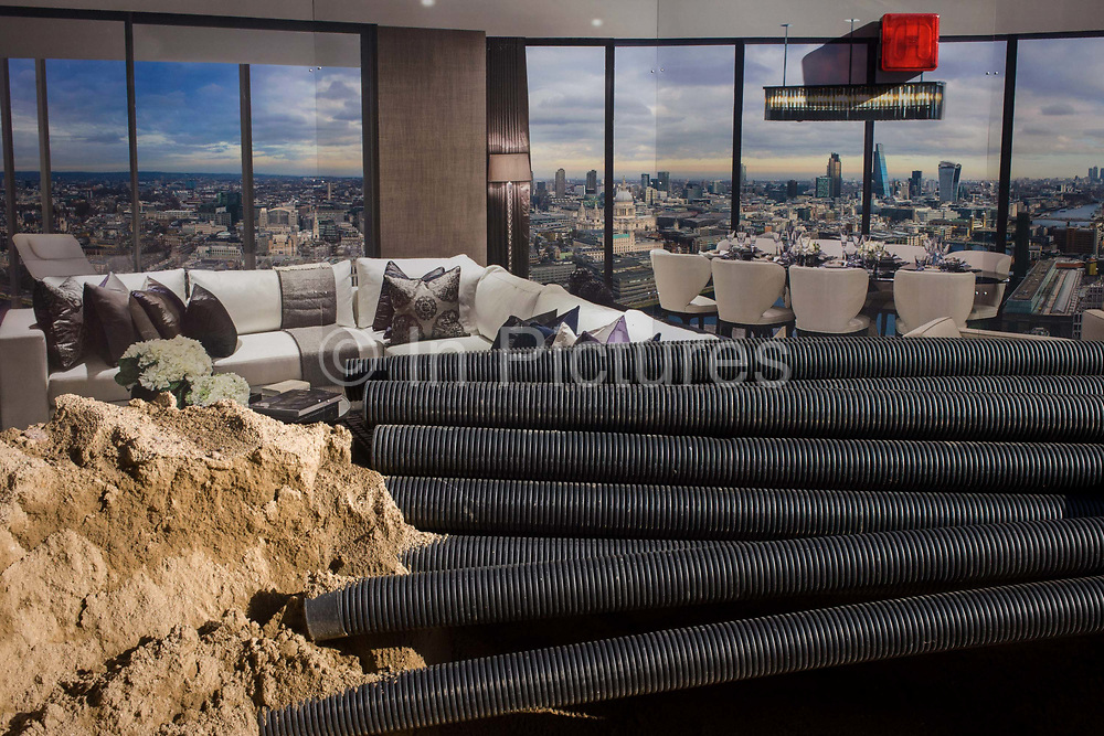 Blackfriars property development marketing suite hoarding and construction materials. Plastic sleeves for cabling plus a pile of sand ballast is seen in the foreground, in front of an incongruous panoramic scene of a luxury apartment with a view over central London. 1 Blackfriars or One Blackfriars, will be a mixed-use development approved for construction at the junction of Blackfriars Road and Stamford Street at Bankside, London. The development make make up a 52-storey tower of a maximum height of 170m and two smaller buildings of 6 and 4 stories respectively. Uses include residential flats, a hotel and retail. In addition a new public space will be created.