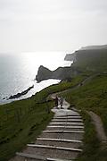 Couple walk up steps from Durdle Door, Jurrassic coast, Dorset, England