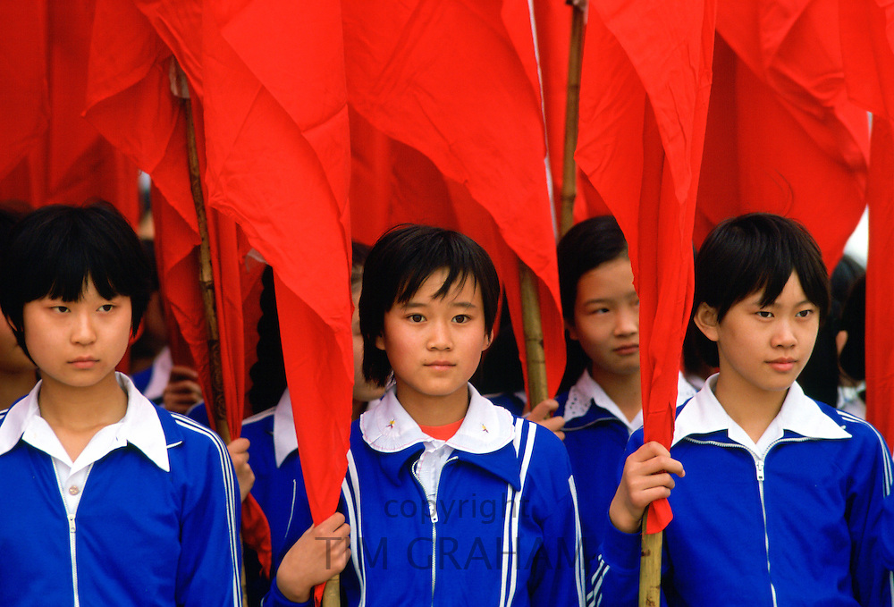 Schoolgirls wearing school uniforms and holding  traditional red flags in Xian, China