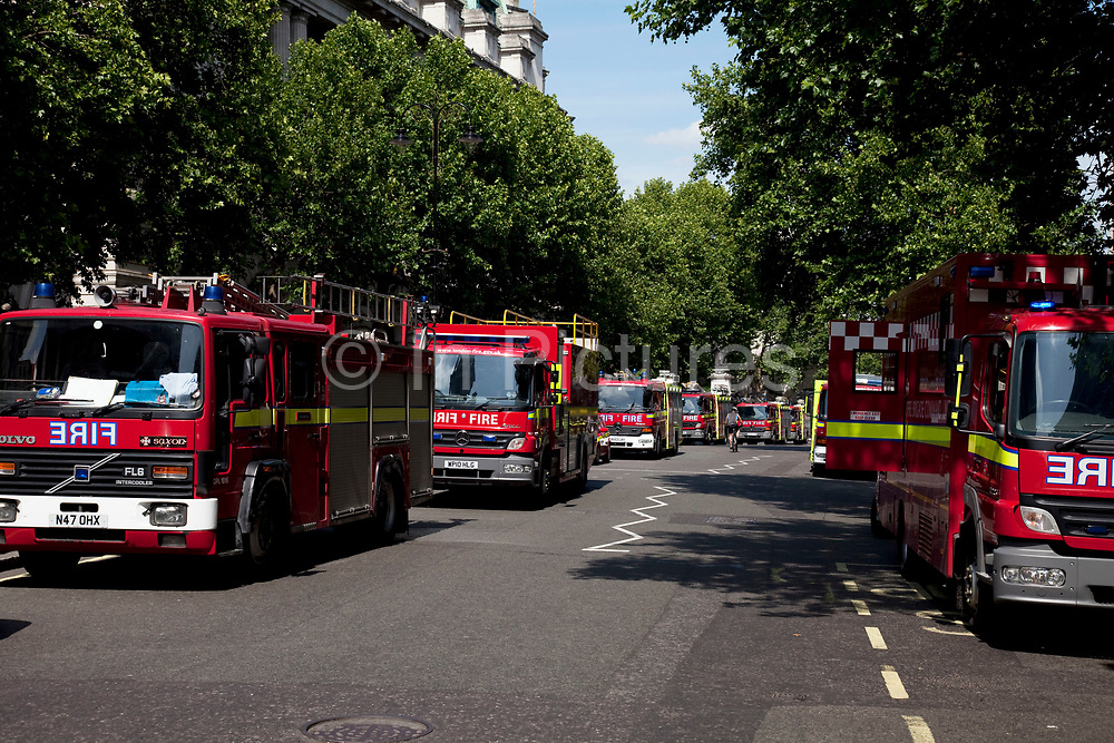 Fire engines attending a fire in a large building which was under refurbishment at Aldwych, in central London. Seventy-five firefighters are tackling the blaze on top of the building in London's West End, at the junction of the Strand and Aldwych. The fire took hold around 11am this morning in a 10-storey building which is currently being converted to a 5-star hotel and 86 luxury flats. Transport for London has closed areas nearby and has put in place diversions.