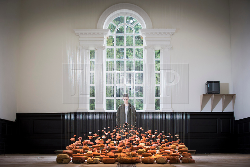 © Licensed to London News Pictures. 29/03/2017. Wakefield UK. Kerry Chase looks at the art work by Cornelia Parkers called Neither From Nor Towards which is made from weathered bricks suspended from the ceiling, the bricks are from a row of houses destroyed when they slipped into the sea on the south-east coast following coastal erosion which is in the Re-constuct exhibition at Yorkshire Sculpture Park. The Yorkshire Sculpture Park has two new exhibitions drawn from the Arts Council Collection. The Re-Construct exhibit featuring Cornelia Parker & Alex Chinneck & the Kaleidoscope exhibition, a new Arts Council Collection touring exhibition. Photo credit: Andrew McCaren/LNP