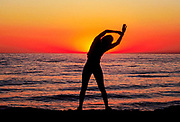 Woman stretches while watching the sunrise over the ocean.