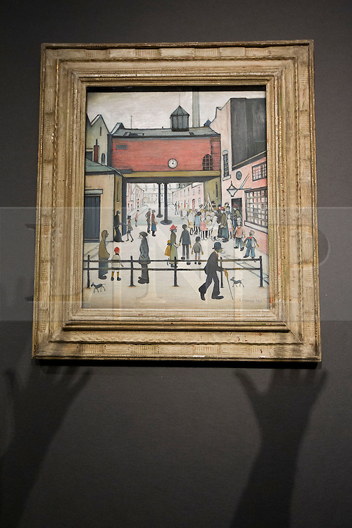 """© Licensed to London News Pictures. 18/11/2013. London, UK. The shadows of a gallery visitor's hands are seen reaching towards """"May Day"""" (GB£700,000 - 1,000,000), painted by influential British artist Laurence Stephen Lowry in 1935, at the press view for a sale of modern British and Irish art at Christie's St James' auction house in London today (18/11/2013). The sale is set to take place on Wednesday the 20th and Thursday the 21st of November 2013. Photo credit: Matt Cetti-Roberts/LNP"""