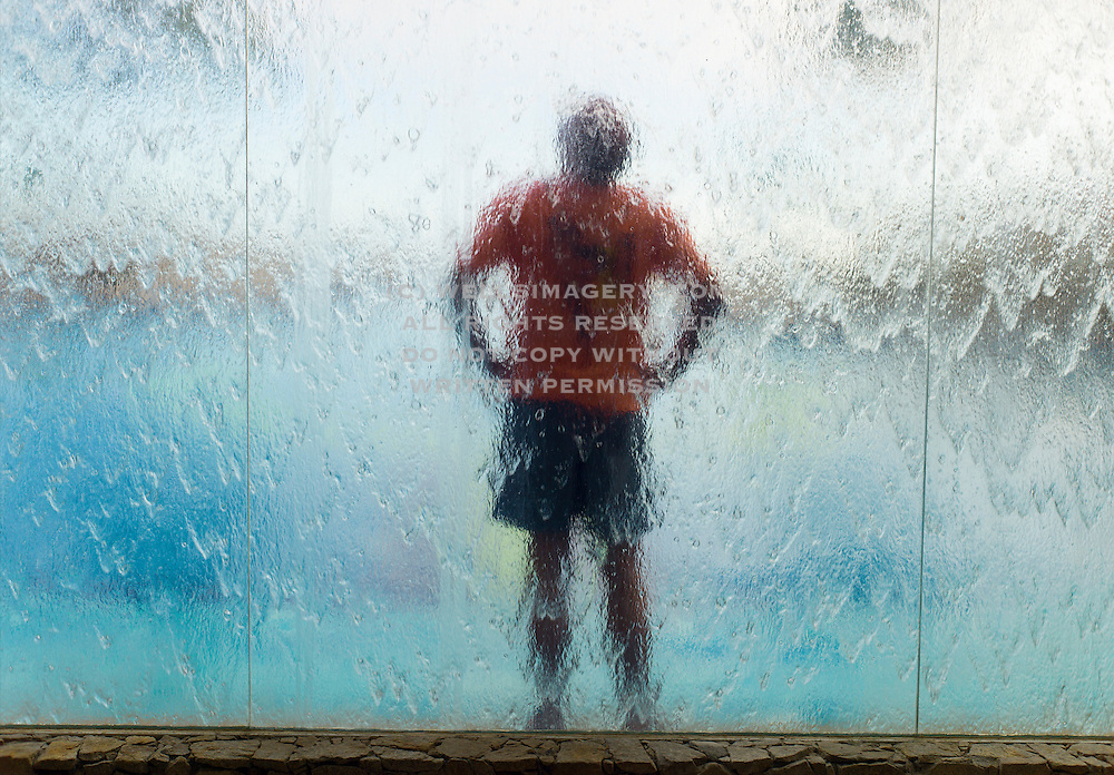 Image of a man under a waterfall in Cabo San Lucas, Baja California Sur, Mexico, model released by Randy Wells
