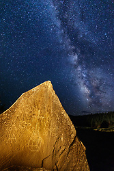 Milky way and tetroglyphs on boulder near Vermeer River in Gonzales Canyon, Vermejo Park Ranch, New Mexico, USA.