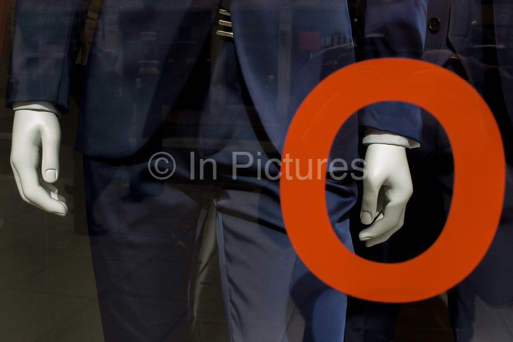Trendy blue suits with red prices and lettering on display in a central London menswear shop. A detail of a circle which appears to highlight the hand of one of three mannequins, encirlcing the fingers and wrist. The shop is on London's Oxford Street, an east to west road long known for clothing and low-cost fashion - and before that, for the route that condemned criminals would take towards the gallows at nearby Tyburn.