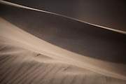 Sand blows through the air over the dunes of Great Sand Dunes National Park, Colorado.