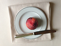 Nectarine on a plate with knife.