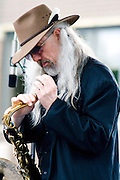 Musician adjusting mouth piece on his saxophone. Grand Old Day Street Fair St Paul Minnesota USA