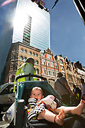 "London, UK. Thursday 5th September 2013. Baby in a push chair in the light. Urgent action in planned to ""cover up"" the Walkie Talkie skyscraper in the City after sunlight reflected from the building melted a car on the streets below. Temperatures have been measured in excess of 50 degrees C, and as much as 70 degrees at it's peak. The 525ft building has been renamed the ""Walkie Scorchie"" after its distinctive concave surfaces reflected a dazzling beam of light which has caused extensive damage to nearby buildings."