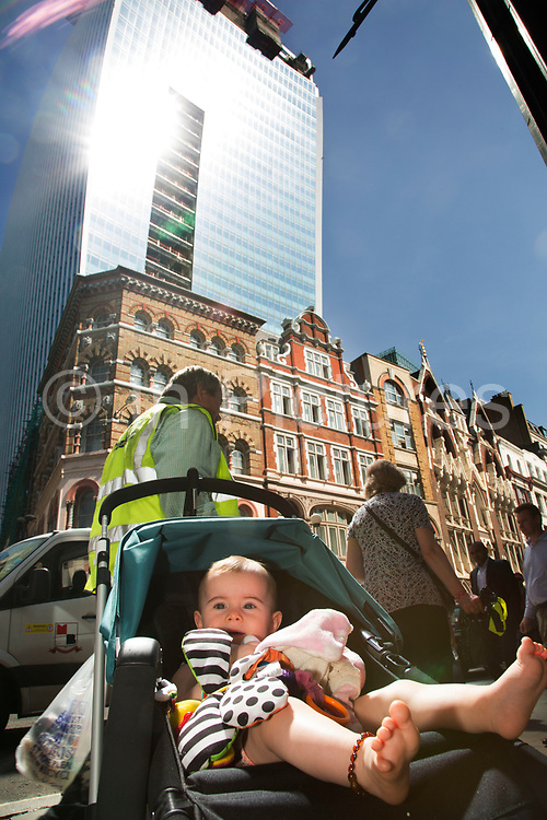"""London, UK. Thursday 5th September 2013. Baby in a push chair in the light. Urgent action in planned to """"cover up"""" the Walkie Talkie skyscraper in the City after sunlight reflected from the building melted a car on the streets below. Temperatures have been measured in excess of 50 degrees C, and as much as 70 degrees at it's peak. The 525ft building has been renamed the """"Walkie Scorchie"""" after its distinctive concave surfaces reflected a dazzling beam of light which has caused extensive damage to nearby buildings."""