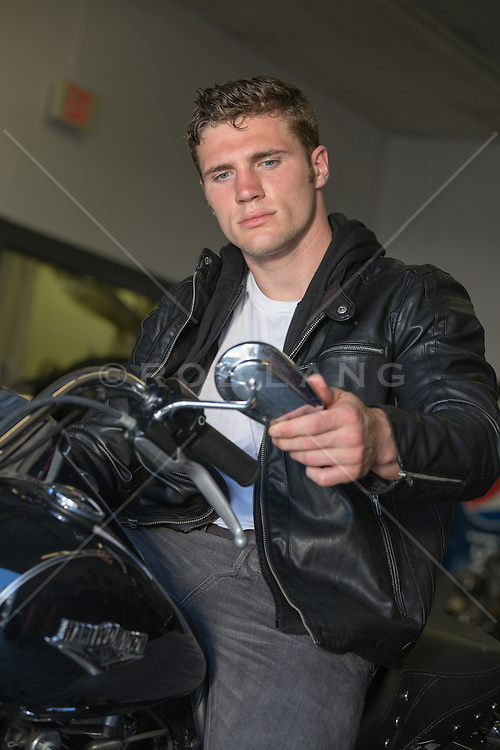 rugged masculine man in a leather jacket on a Harley Davidson Motorcycle looking in the rear view mirror