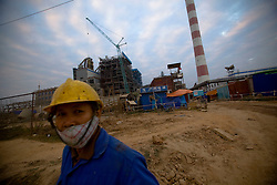 Workers are seen at  the Haiphong Thermal Power Plant construction site in Trung Son, Vietnam, Nov. 21, 2009. Dongfang Electric, a large Chinese contractor, and Marubeni, a Japanese company, won the $500-million contract in 2005. China, famous for its export of cheap goods, is increasingly known around the world for shipping out cheap labor.