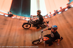 Cody Ives reaches out to give his little brother Kyle a pat on the back as they race around the inside of the Ives Brothers Wall of Death at the Harley-Davidson display at the Daytona Speedway during Daytona Bike Week. Daytona Beach, FL. USA. Monday March 13, 2017. Photography ©2017 Michael Lichter.