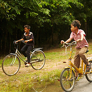 Young boys riding bycicles at one of the roads that connects the temples of Angkor.