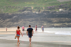 Holidaymakers walk along Fistral Beach in Newquay, Cornwall.