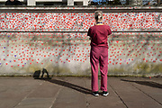 NHS staff look at the red hearts that form the National Covid Memorial Wall, a tribute to the 150,000-plus British victims of the Coronavirus pandemic on 30th March 2021, in London, United Kingdom. Bereaved family and friends of Covid-19 victims have started working on the wall located outside St Thomas Hospital.
