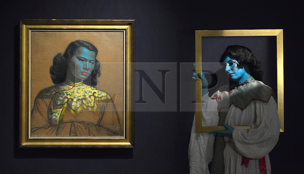 """© Licensed to London News Pictures. 18/03/2013. London, UK Cabaret singer Tricity Vogue, whose successful Edinburgh Fringe Theatre Festival performances were inspired by 'Chinese Girl' poses with the original painting. Press call before the auction of """"Chinese Girl"""" by Vladimir Tretchikoff at Bonhams in London today 18th March 2013. The painting is said to be the most widely reproduced and recognisable painting in the world because of its wide reproduction in 1950's art prints. It is expected to fetch 300,000-500,000 GBP at auction on the 20th March. Photo credit : Stephen Simpson/LNP"""