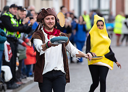 © Licensed to London News Pictures. 05/03/2019. Lichfield, Staffordshire, UK. The annual Shrove Tuesday pancake race taking place in Bore Street in the City Centre of Lichfield. Pictured, winner of the fancy dress race, Richard Barber. The event features races for men, women, children and those in fancy dress. The runners are supported by the voice of Town Crier Ken Knowles and the overall winner walks away with a brass and wooden Shrove Tuesday trophy. Photo credit: Dave Warren/LNP