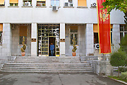 Skupstina Republica Crna Gora, the parliament assembly of Montenegro, main entrance with glass, brass and stone, on the Sveti Petra Saint Peter boulevard. A man in blue walking out. Montenegrin banner flag in red with eagle Podgorica capital. Montenegro, Balkan, Europe.