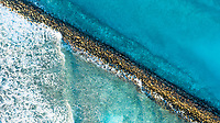 Aerial view of waves breaking at the stone walls of the harbour entry of  the local / inhabited island Vashafaru, Haa Alif Atoll, Maldives, Indian Ocean
