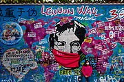 A young woman wearing a face-mask is getting a photograph at the Prague Lennon Wall in-front of a John Lennon graffiti. Once a normal wall, since the 1980s it has been filled with John Lennon-inspired graffiti and pieces of lyrics from Beatles' songs. The Czech government lowered the security measures and as of Monday 25 May 2020, wearing of protective masks will be mandatory only in the interiors of buildings other than the place of residence and in public transport.