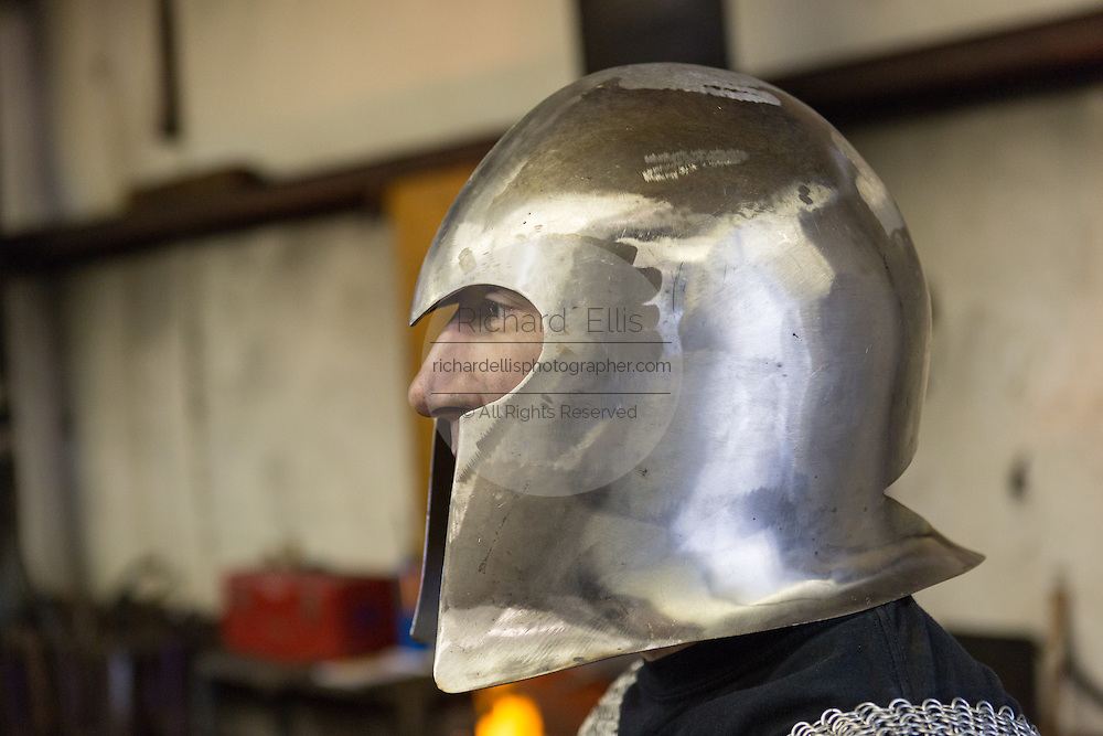 Blacksmith Frank Verga wearing a medieval helmet he made in his metal working shop in Charleston, SC
