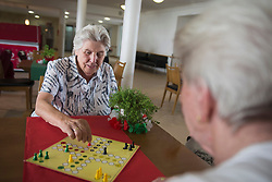 Senior women playing ludo board game at rest home, Bavaria, Germany, Europe