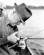 Gordon MacQuarrie oiling a fishing reel, 1940.