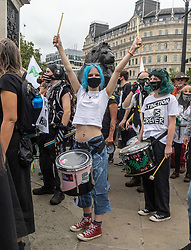 """Licensed to London News Pictures. 23/08/202. London, UK. A young climate change protester cheers as she plays the drums as Extinction Rebellion (XR), arrive in Trafalgar Square, London for the start of a 14 day protest with disruptive action and possible occupations of buildings and services. The protest, """"The Impossible Rebellion"""", want the government to implement their demand to stop all new fossil fuel investment immediately. Photo credit: Alex Lentati/LNP"""
